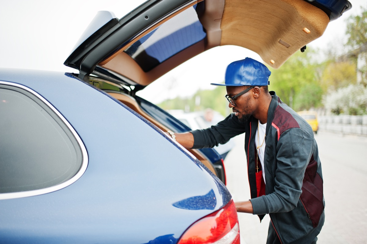 man putting emergency items in his car trunk, safety tips