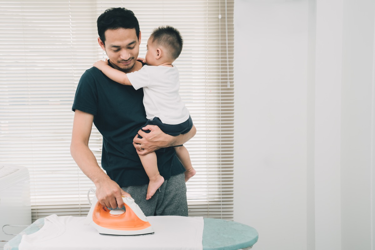 Father Ironing Clothes With a Baby in His Arms How Parenting Has Changed
