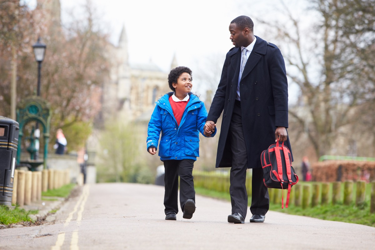 father picking up his child son from school and carrying his backpack, parent divorce