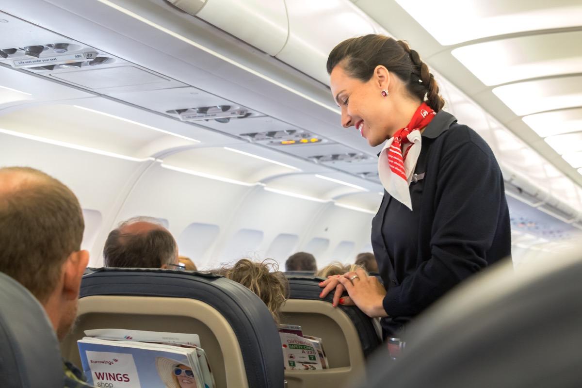 flight attendant talking to man