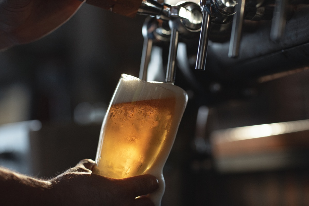 Fresh beer filling the glass directly from the tap. With extra foam spilling over glass.