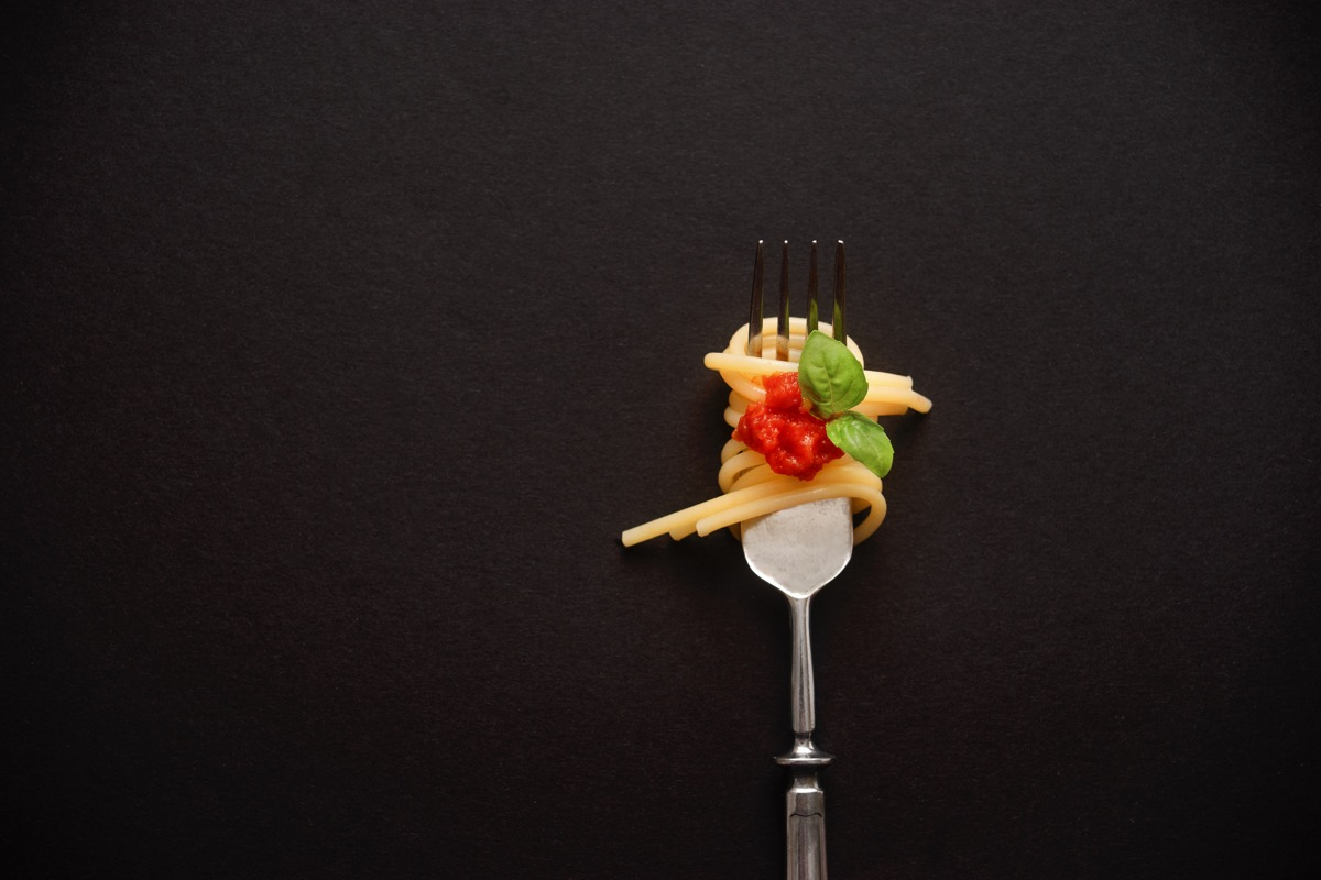 Top view of fork with spaghetti, tomato, and basil on black. Close up. Copy space