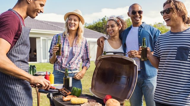 Friends Hanging Out by the Grill at a Barbecue BBQ Etiquette Mistakes