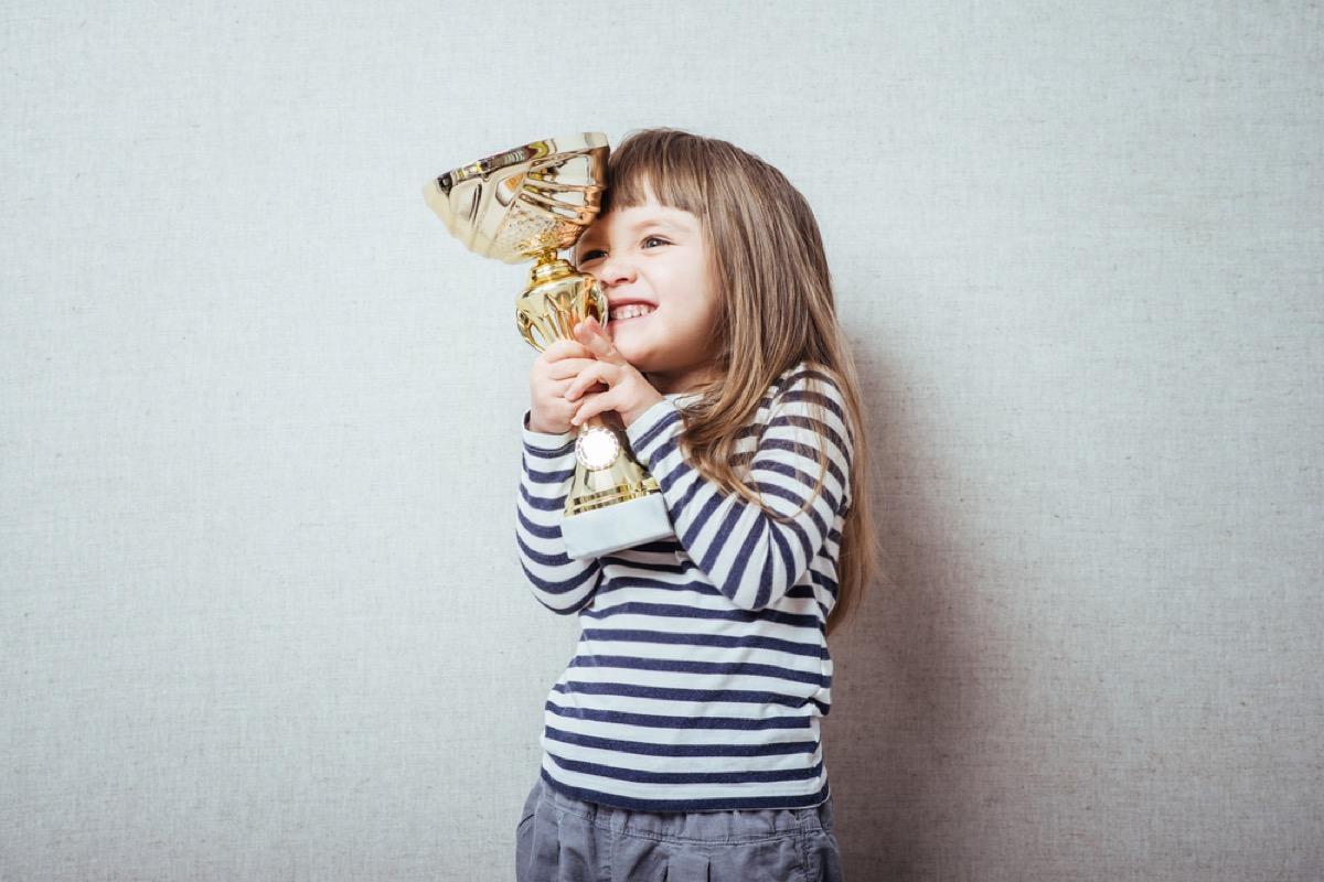 little girl holding trophy, bad parenting