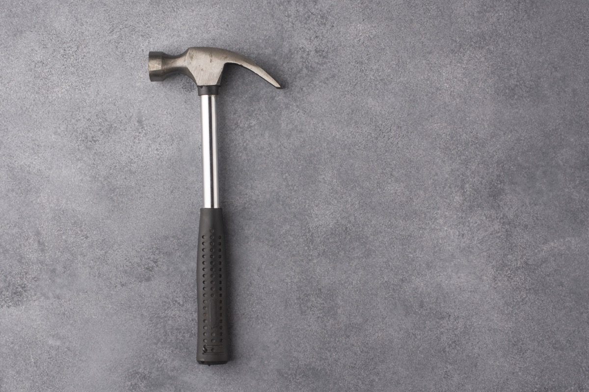 Hammer on a gray background. View from above. Free space for an inscription.