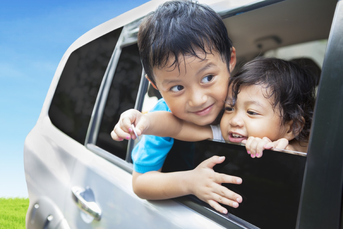 young boy and girl siblings leaning out of car window, bad parenting advice