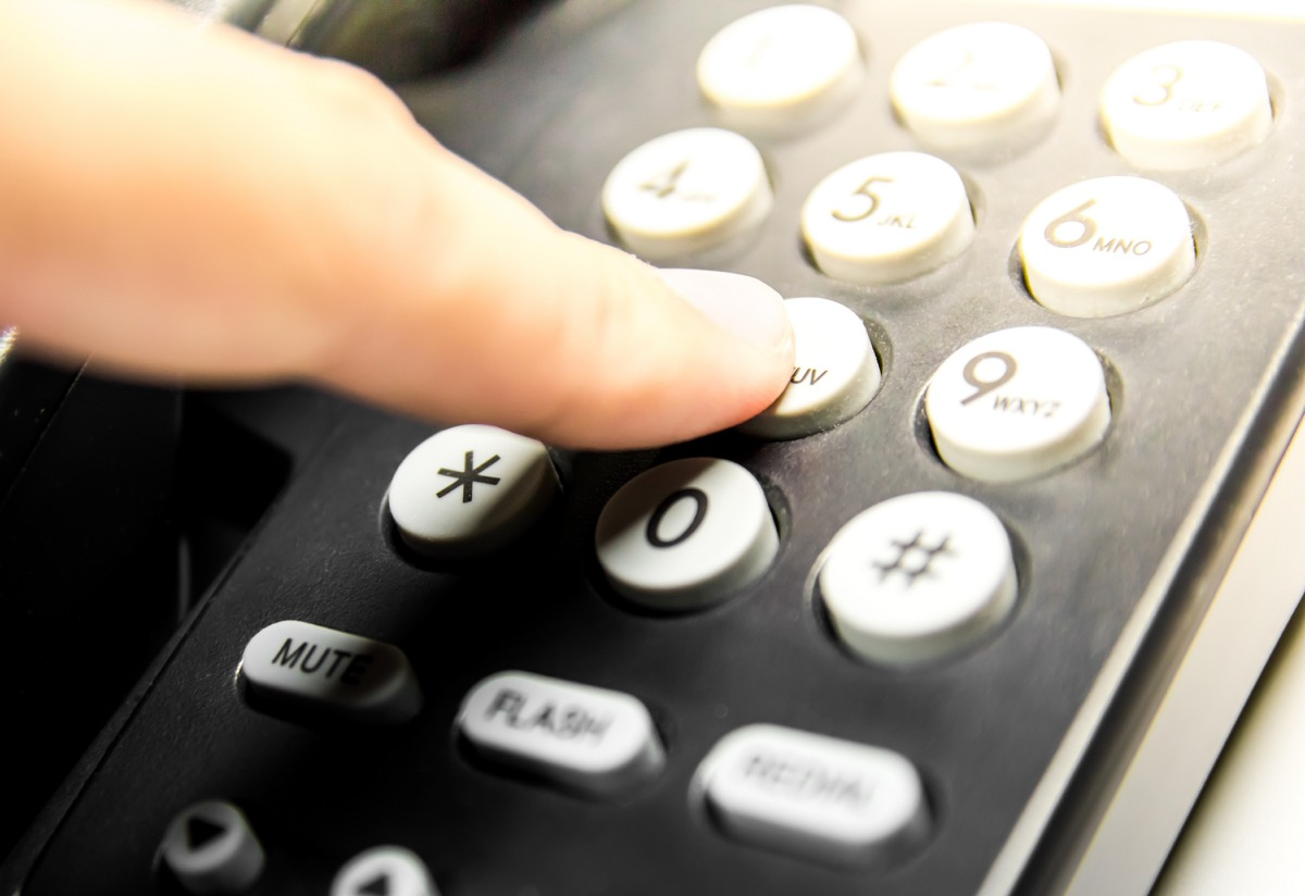 Finger press number button keypad on black telephone for call in flare light warm tone theme.