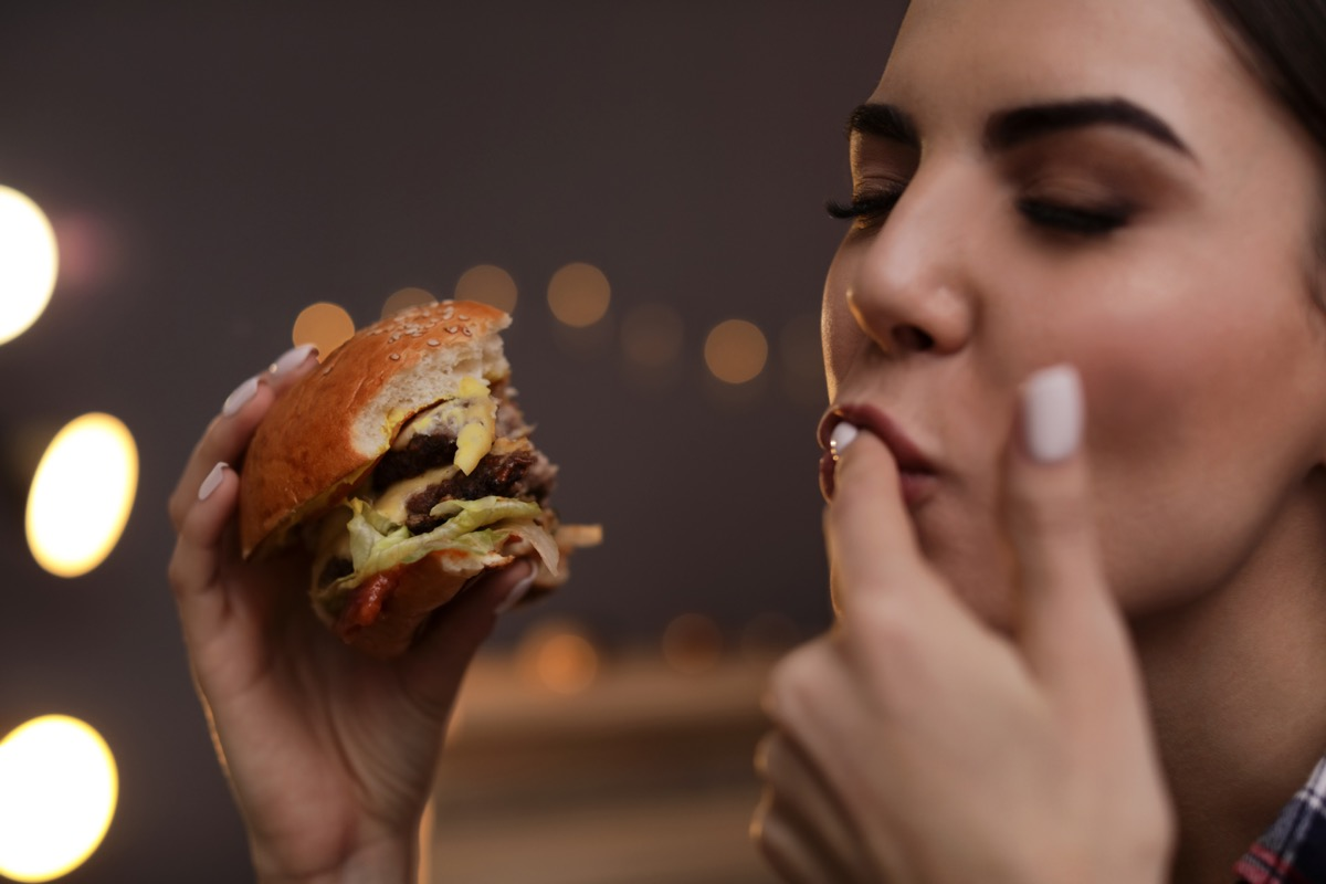 Woman Licking Her Fingers While Enjoying a Burger BBQ Etiquette Mistakes