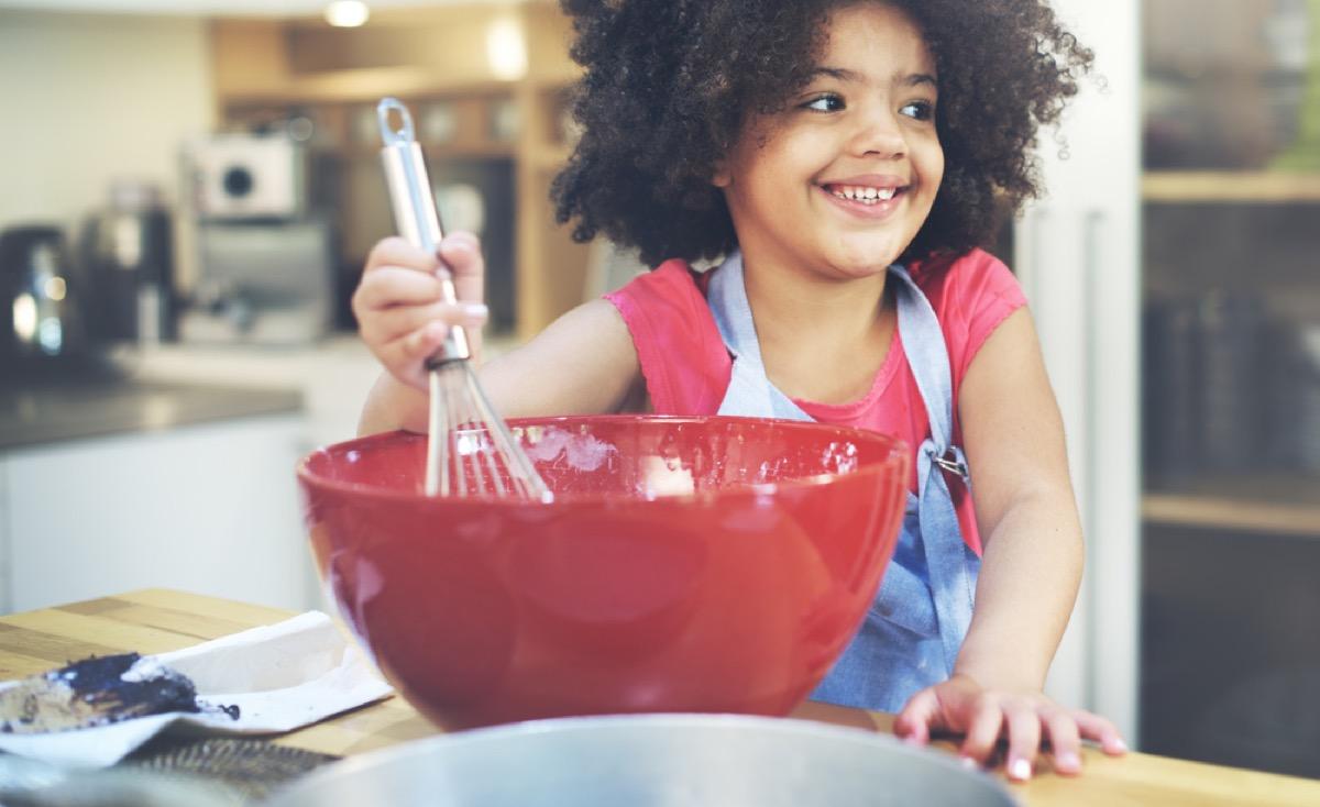little girl whisking cake batter, fire prevention tips