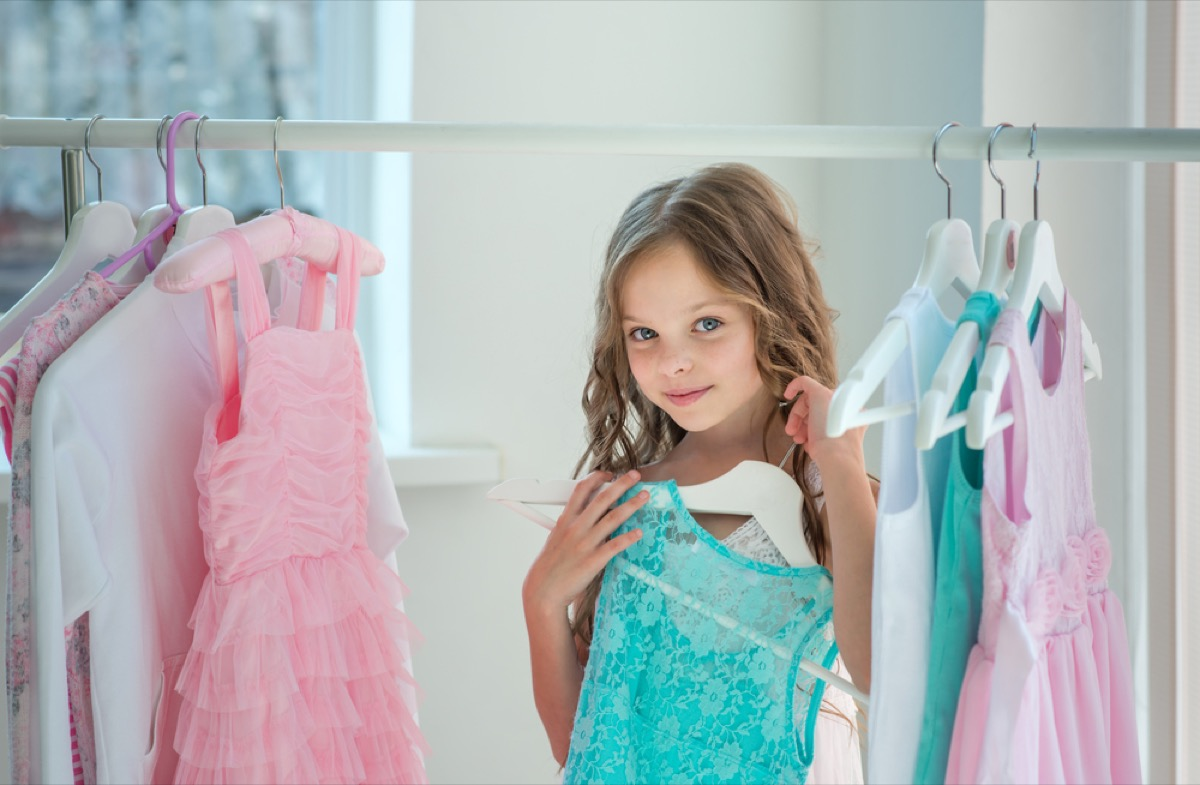 little girl in closet holding dress in closet, parenting tips