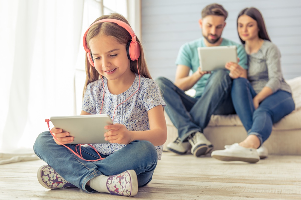 young girl with headphones on tablet, ways parenting has changed