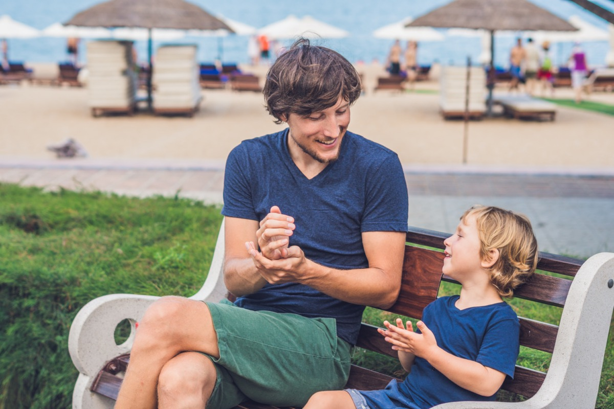 young white man in blue t-shirt and small boy using hand sanitizer on a bench near a beach