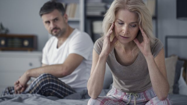 Woman holds head in hands as husband looks on in bed