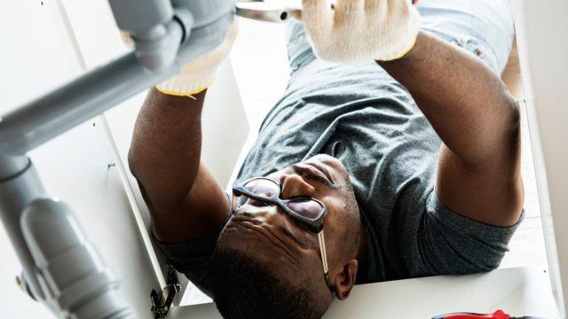 black man fixing sink