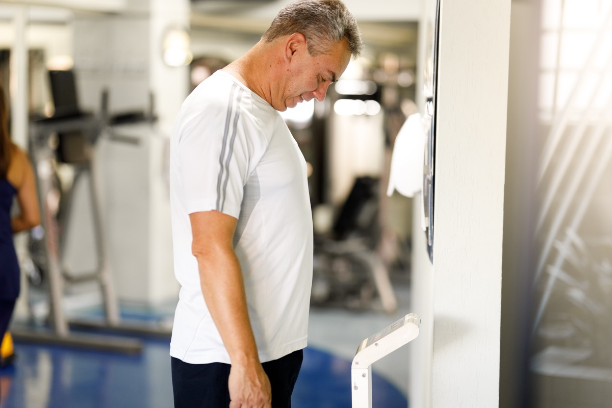 Man weighing himself on a scale at the gym