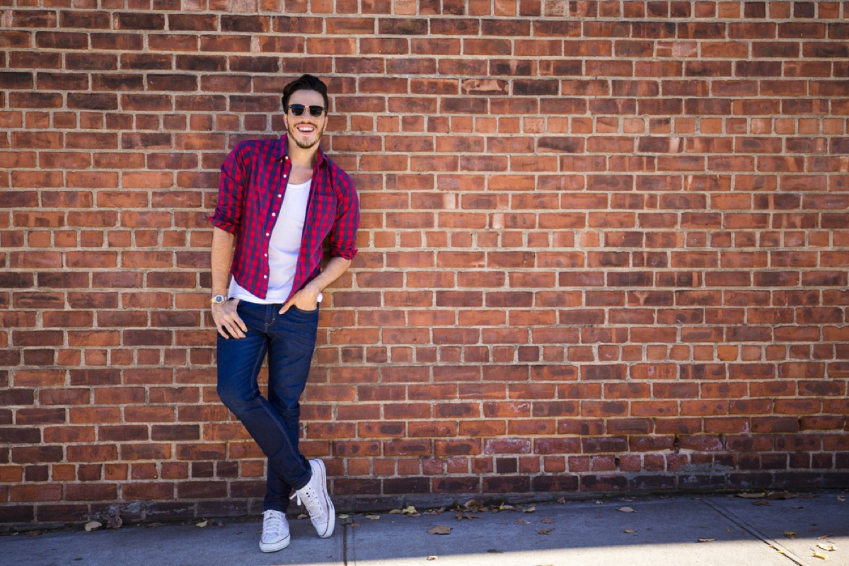 man in skinny jeans standing against brick wall