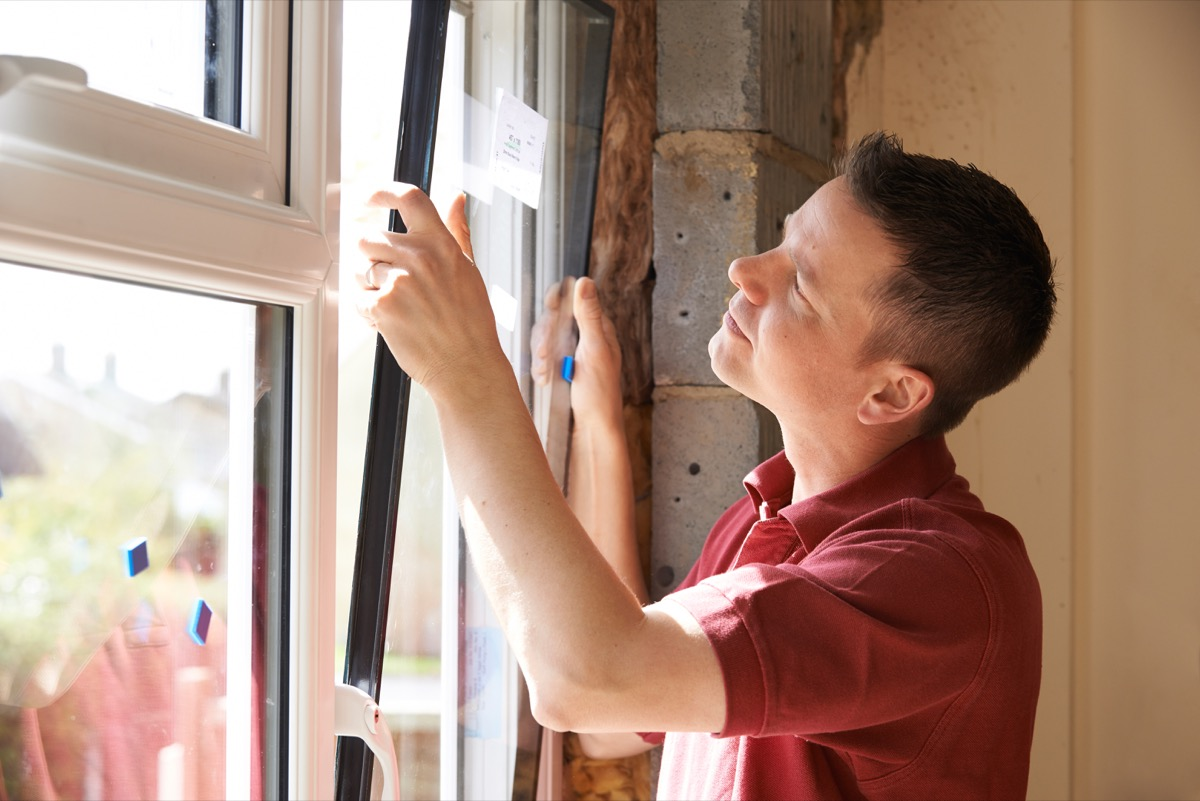 man installing energy efficient windows ways to bring down a/c bill