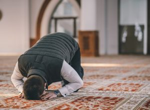 Muslim Man Kneeling on the Ground and Praying for Ramadan