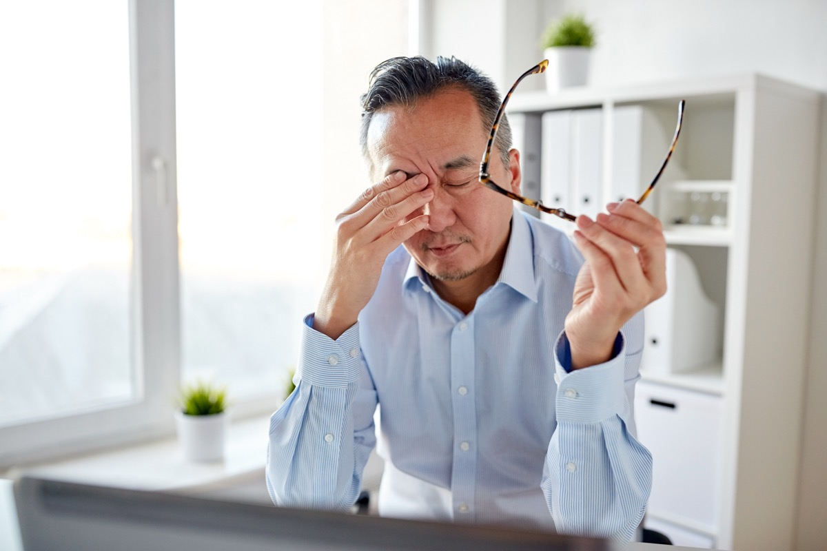 Mature asian man rubbing his eyes with tiredness