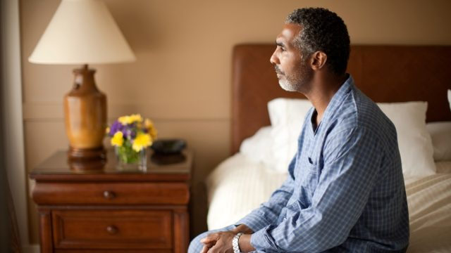 man sitting on bed can't sleep, over 50 fitness