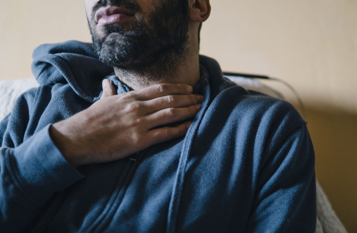 Young adult man suffering from sore throat