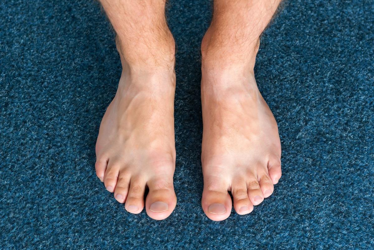 man's bare feet on blue carpet