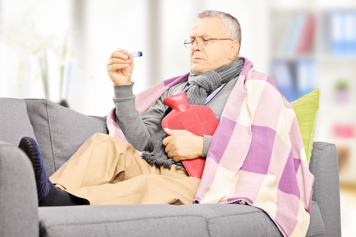 Older man sick on the couch with a fever