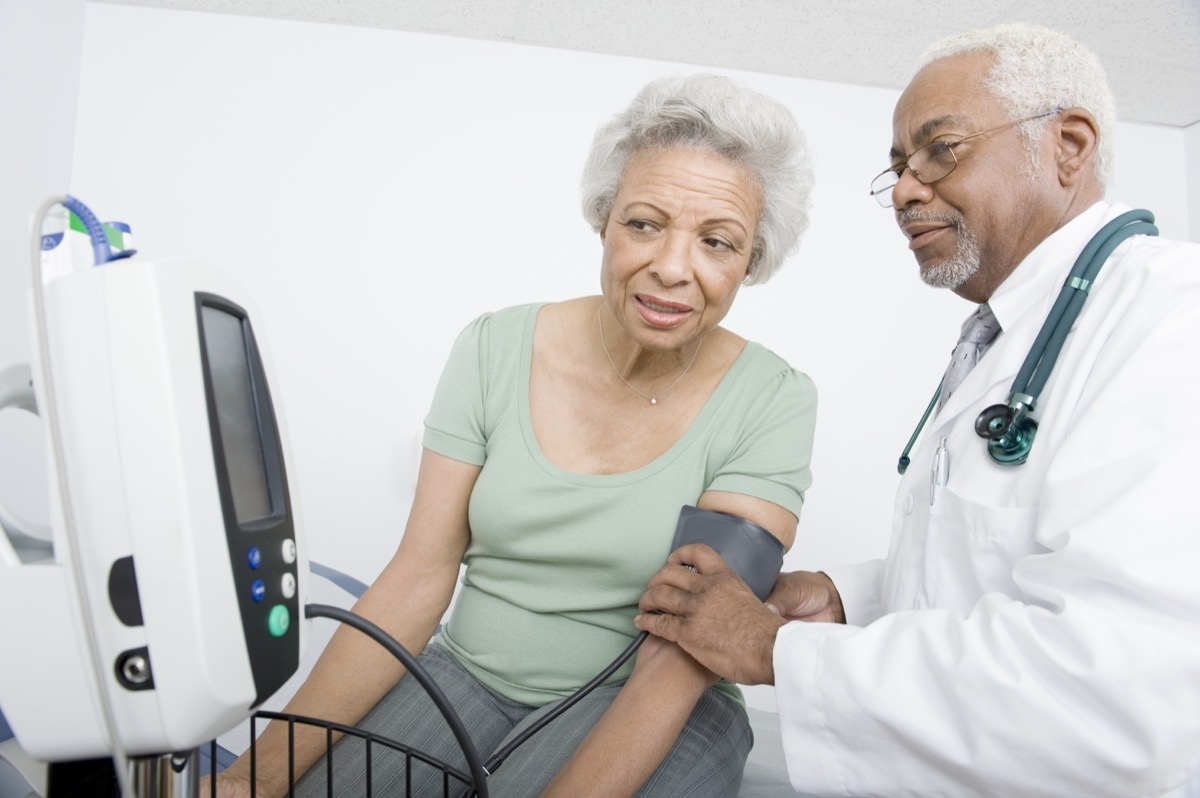 woman and doctor taking her blood pressure looking at the screen Alzheimer's Risk