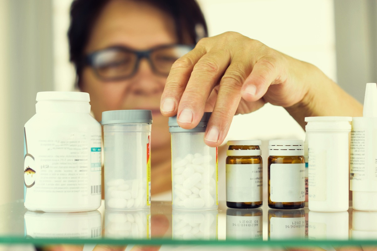 woman looking through her medications in her medicine cabinet, things you should never store in your attic