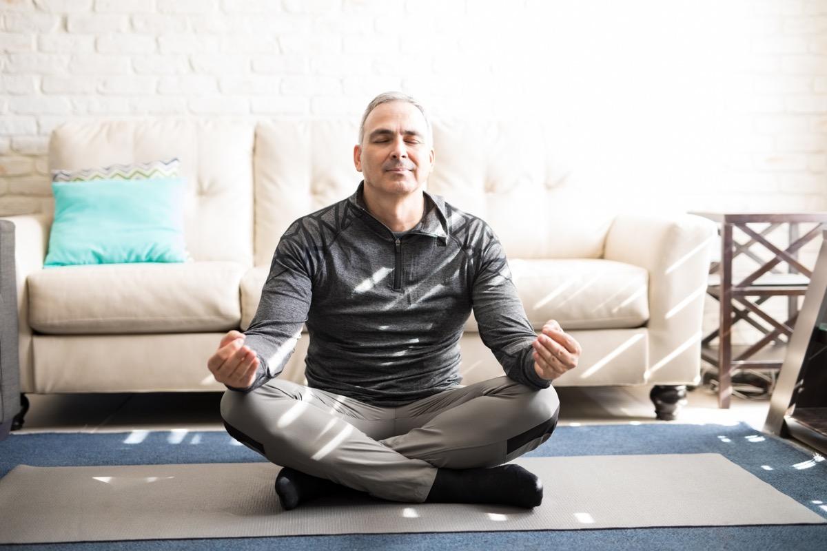 Man meditating in living room