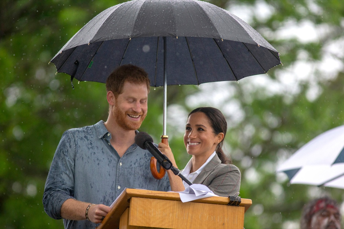 The Duchess of Sussex holds an umbrella as the Duke of Sussex makes a speech at a community picnic in Victoria Park in Dubbo, New South Wales, on the second day of the royal couple's visit to Australia.