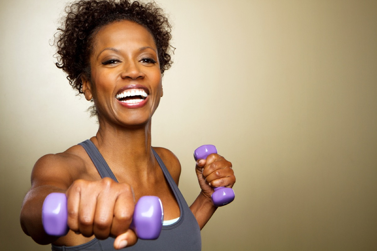 happy older woman working out with dumbbells, look better after 40