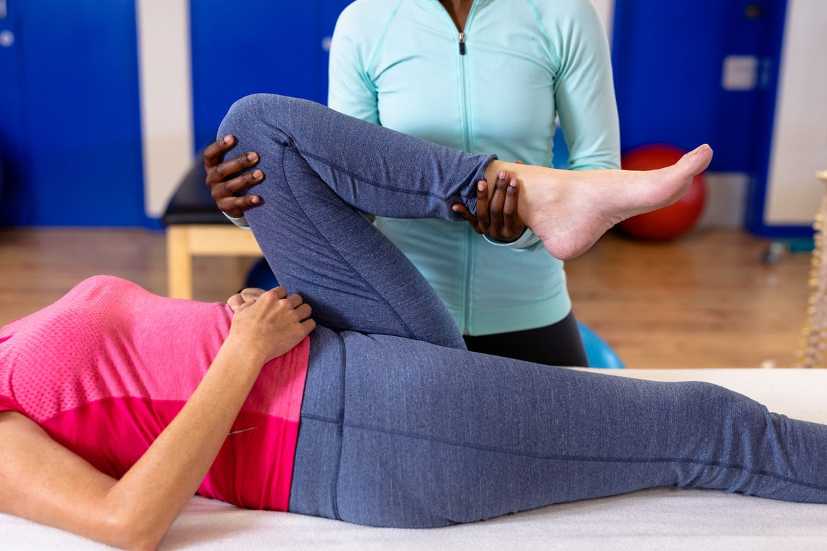 Trainer stretching older woman