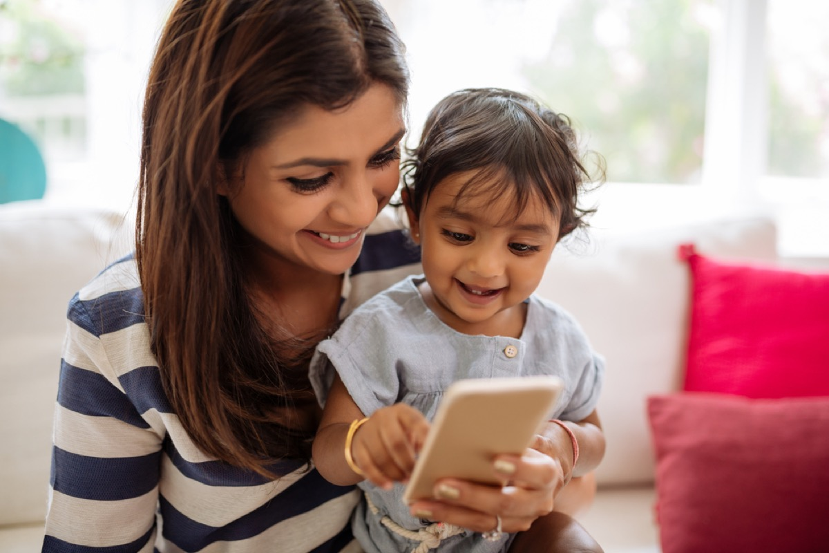 woman holding baby and cell phone, ways parenting has changed