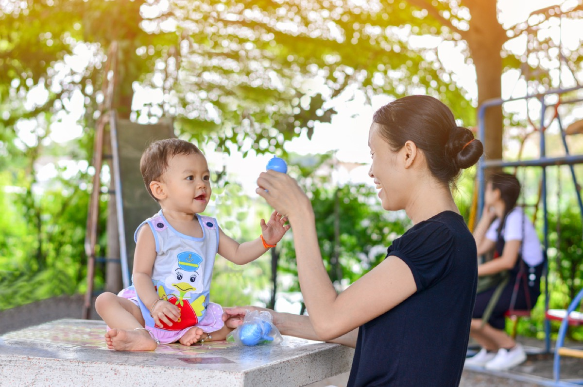 mom entertaining child with toy, parenting tips