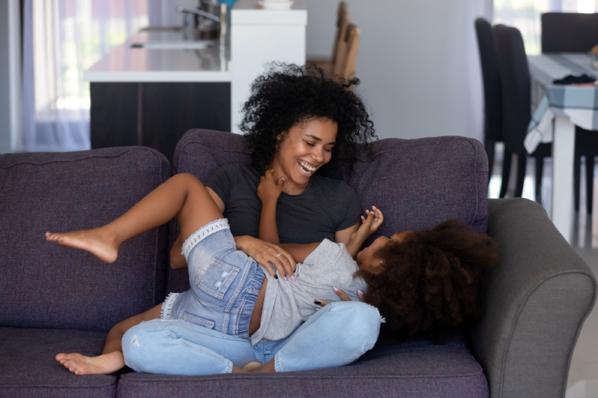 mom tickling daughter on couch, prepare children for divorce