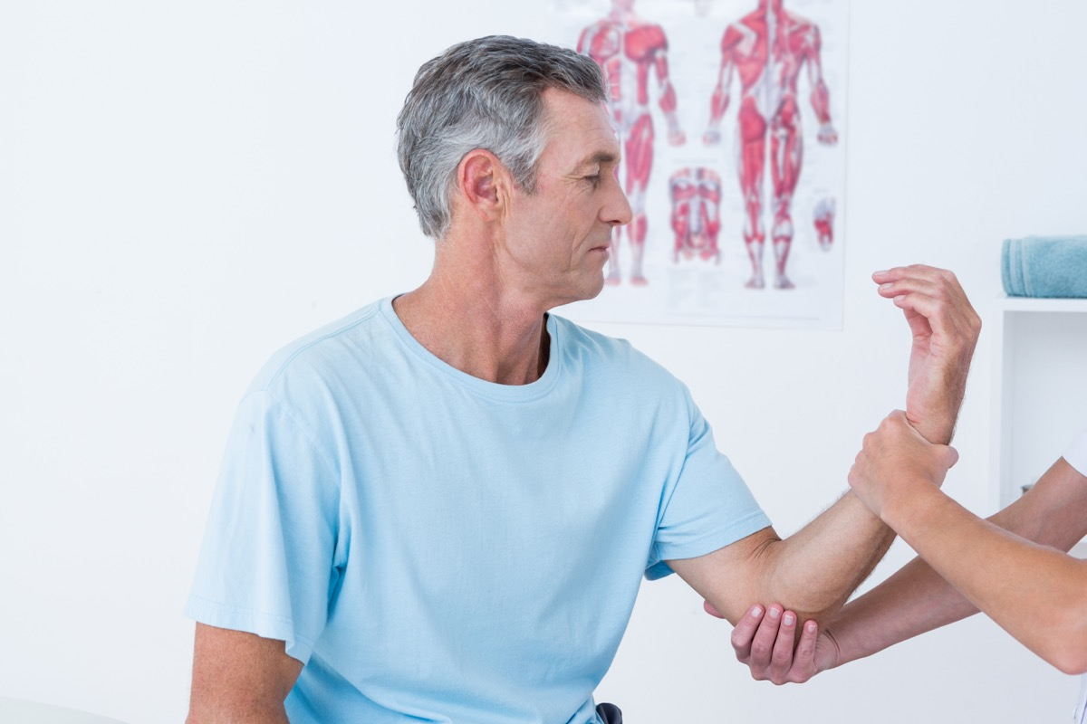doctor examining muscle of patient, health questions after 50