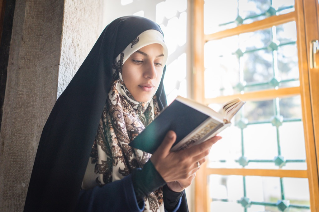Muslim Woman Reading at a Mosque Ways Ramadan is Celebrated