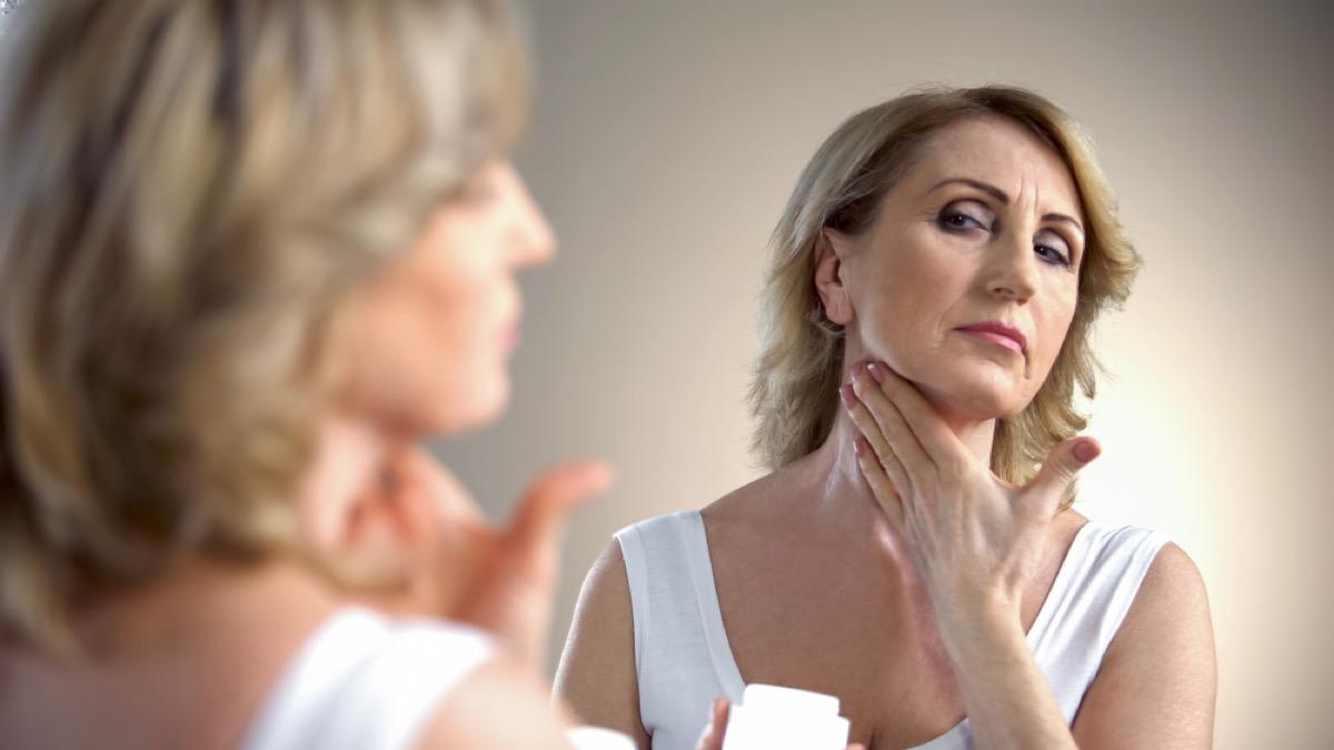 older woman applying neck cream, look better after 40