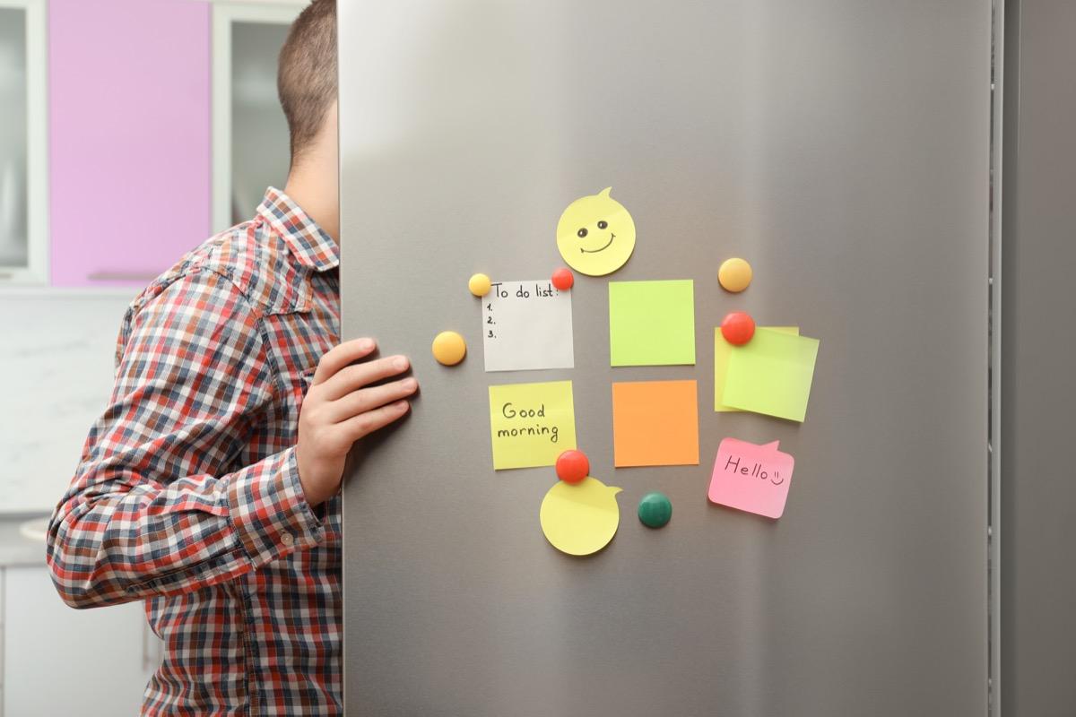 man opening fridge door with note on it
