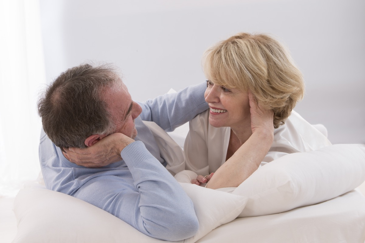 older couple smiling and happy together in bed, health questions after 50