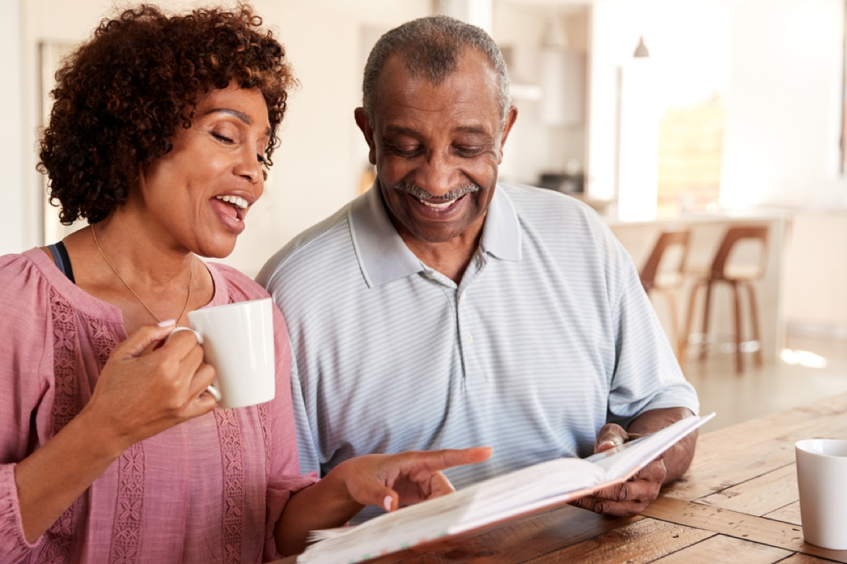 couple looking through photo album over coffee, things husband should notice
