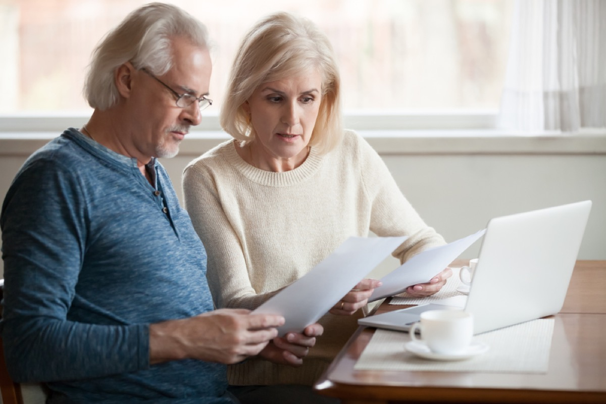 older couple going over financial documents, things you should never say to your spouse