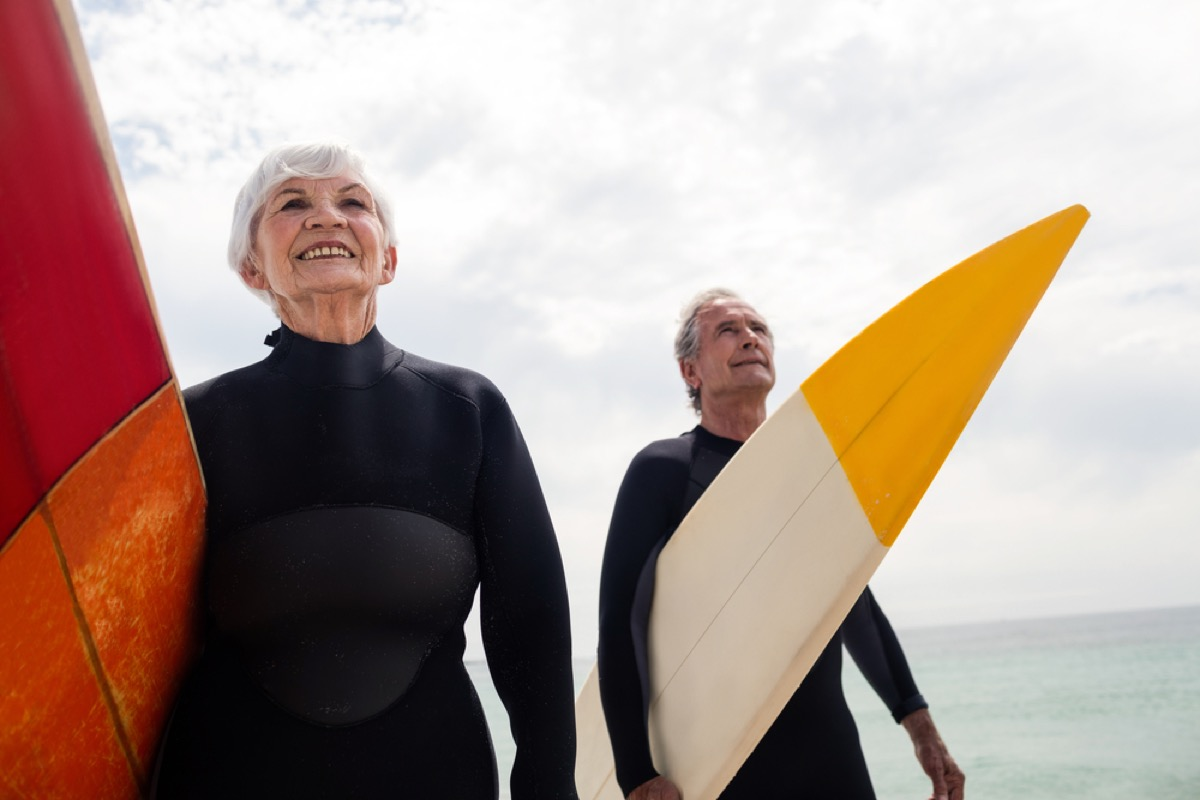 older couple on the beach in wetsuits with surfboards, better wife after 40