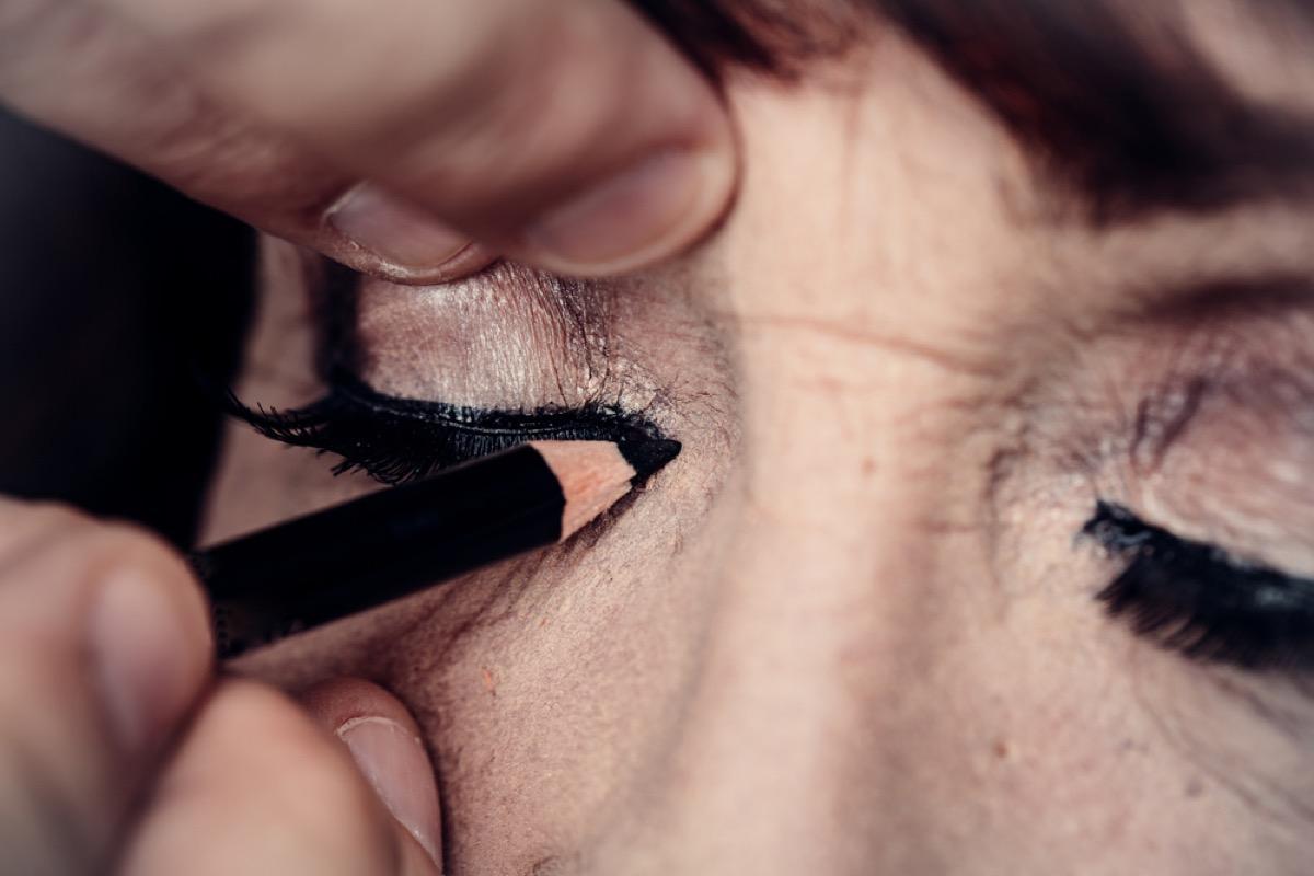older woman applying eye makeup, look better after 40