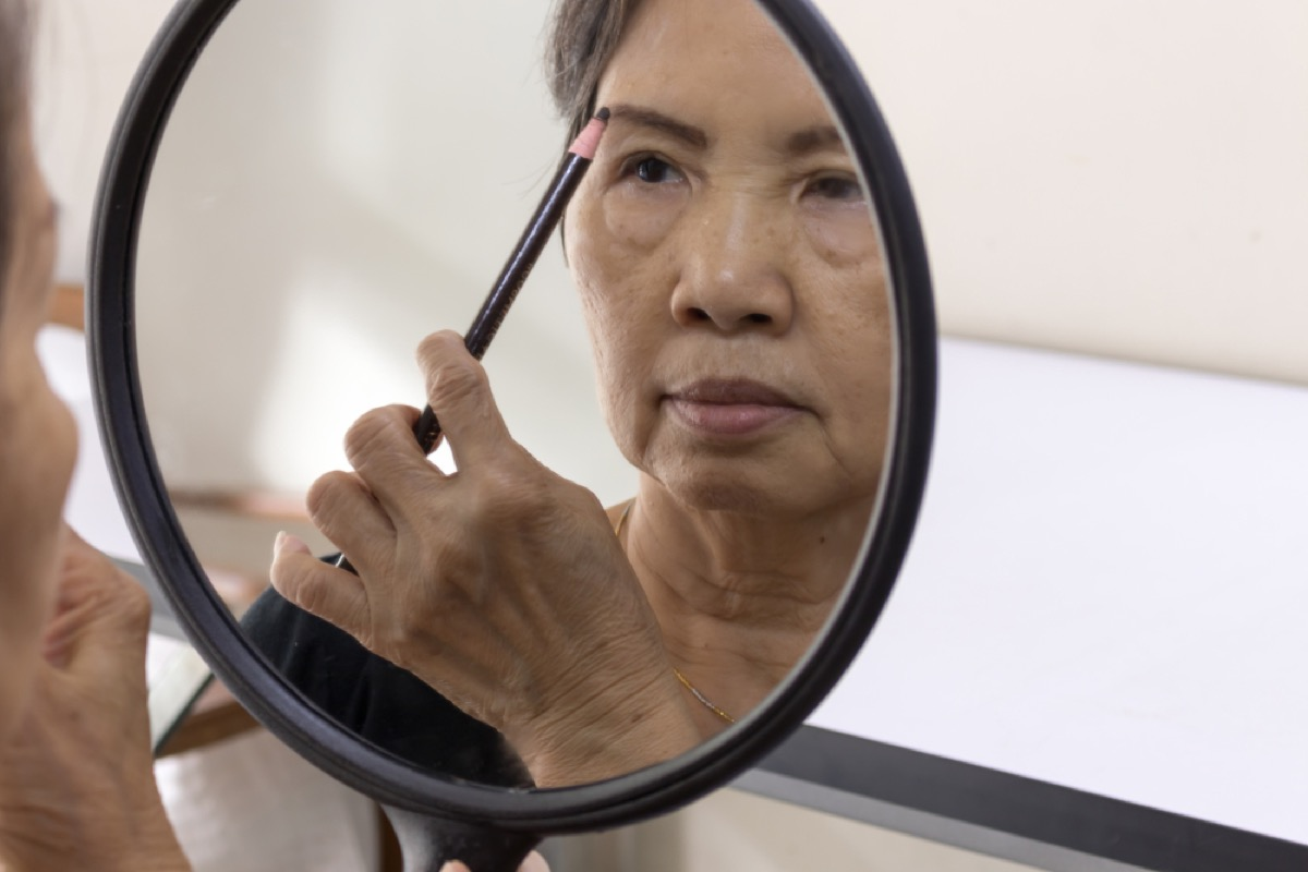 older woman applying eyebrow pencil, look better after 40