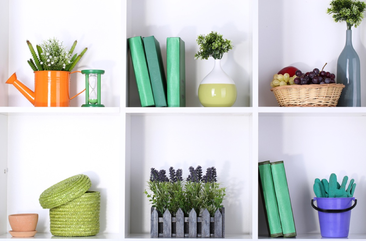 open shelves with green books and plants, joanna gaines tips