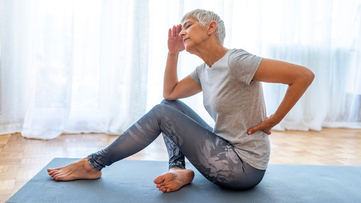 Woman with lower back pain on yoga mat