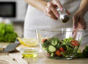 Woman putting salt on salad