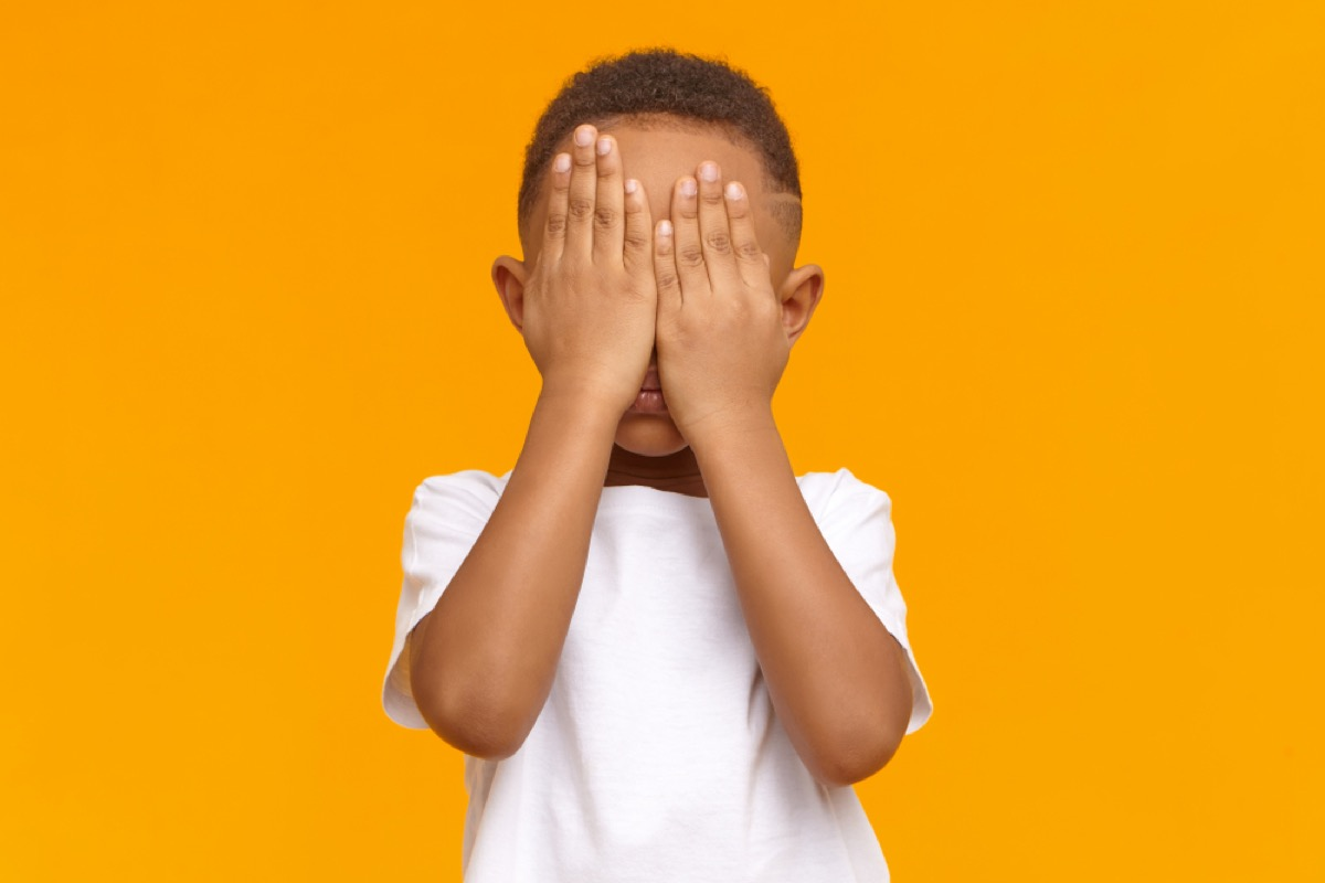 little boy covering face with hands, parenting myths